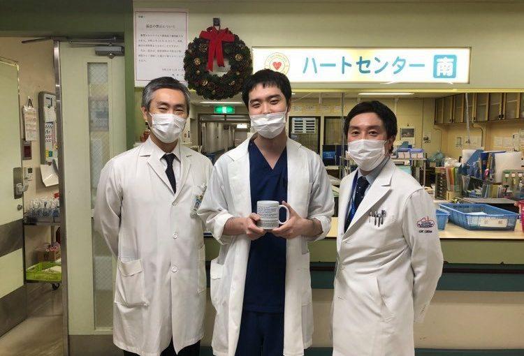 明石教授と木田准教授との記念撮影。学位論文のプリントされたオリジナルマグカップとともに。